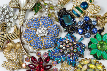 Collection of colorful vintage rhinestone brooches, on white, horizontal aspect