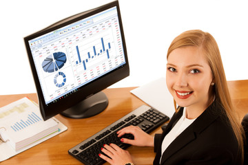 Beautiful young business woman works in office with big copy space on monitor display