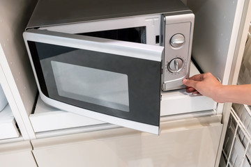 Woman's Hands pressing button to open microwave door
