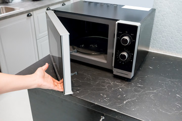 Woman's Hands open microwave door