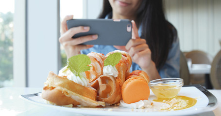 Woman taking photo with cellphone on her waffle