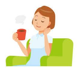 A woman nurse in a white uniform sits on a sofa and is drinking coffee