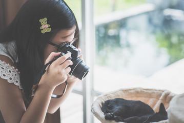 Asian Girl taking a photo of black kitten sleeping on cat tower