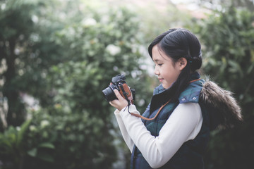 Beautiful Asian girl  in warm clothes with retro  camera shooting a photo in the park