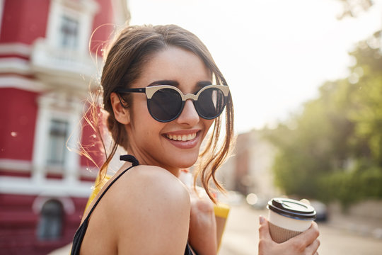 Soft focus. Lifestyle concept. Close up portrait of joyful young attractive dark-haired caucasian woman in sunglasses and black outfit smiling with teeth, drinking coffee, holding bags with clothes