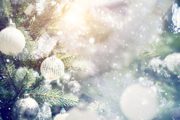 Fototapete - Christmas holiday background. Silver and white bauble hanging from a decorated on christmas tree with bokeh and snow, copy space.
