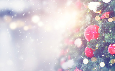 Fototapete - Christmas holiday background. Red bauble hanging from a decorated on christmas tree with bokeh and snow, copy space.