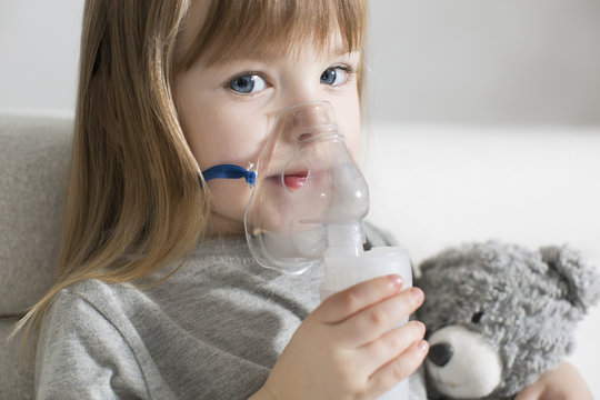 Little girl making inhalation with nebulizer at home. child asthma inhaler inhalation nebulizer steam sick cough concept