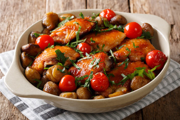 Spicy roast chicken with chestnuts, greens and tomatoes close-up in a dish. horizontal