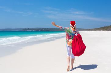 Christmas in Australia - festive woman walking along idyllic beach summer