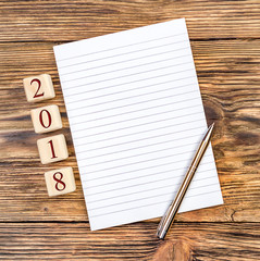 Blank notepad with pen and 2018 written by wooden cubes on the table.