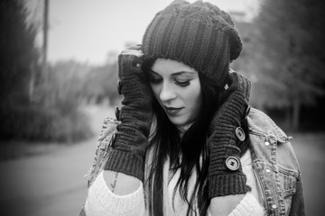 Modern stylish student girl at winter day in Europe. Woman in knitted brown hat and gloves. Lady in fashionable vintage denim and sweater. Walk with good mood