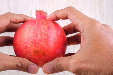 Hand holding pomegranate fruit  over wood  grain  background . Healthy eating concept.