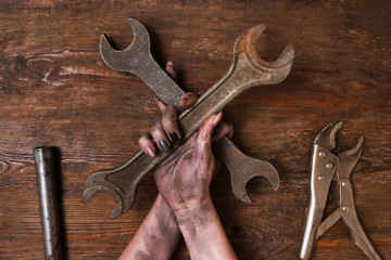 Two crossed spanners on wooden background in woman's hands. Service repair and maintenance concept