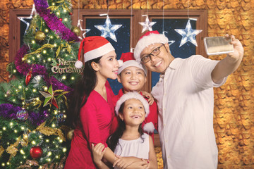 Cheerful family taking picture with Christmas tree