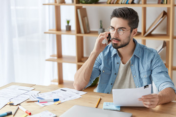 Portrait of handsome bearded young fashionable male has phone conversation, holds documents, sits at wooden table. Stylish hipster male tries to solve financial problems, sits over office interior