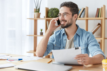 Cheerful bearded man wears denim shirt, has phone conversation with colleague, sits in coworking space, discuss business project. Young male manager talks with clients, holds sheet of paper.