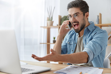 Annoyed male enterpreneur looks angrily into laptop computer, has conversation with business partner via mobile phone, being annoyed as he didn` t prepare business report for meeting with investors
