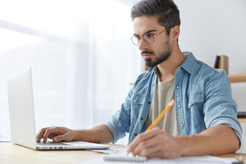 Attractive unshaven stylish young male wears denim shirt and spectacles, looks attentively at laptop computer as studies necessary information, reads notes at blank paper, concentrated on work