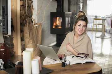 Young beautiful woman in the living room sits on the floor and communicates with friends over the computer, covered with a blanket for the cold in the back of the fireplace