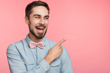 People and advertising concept. Good looking young unshaven male wears festive clothes as celebrates special occasion in life, points with fore finger at copy space of pink blank studio wall