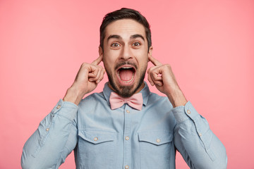 Portrait of cheerful overjoyed happy male plugs ears as hears loud music, being on disco party, wears formal shirt with tie bow, screams loudly, isolated over pink background. People and joy concept