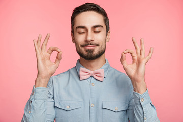 Concentrated bearded man wears formal shirt and tie bow, makes ok sign, closes eyes, shows approval or tries to relax, poses against pink background, meditates indoor. People, body language concept