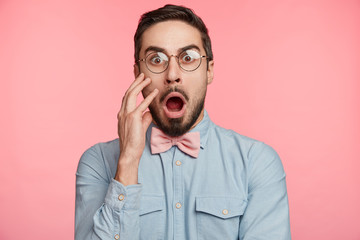 Shocked young handsome man stares through spectacles, being surprised to hear bad news or frightened of future difficuties on work, poses against pink background. Emotional bearded attractive guy Wall mural