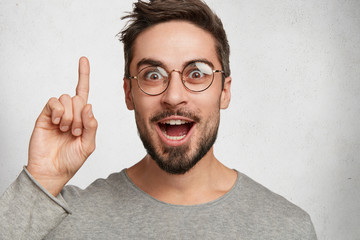 Horizontal shot of bearded amazed handsome guy has excited expression, raises index finger, glad to recieve good idea about improvement his scientific work. Happy pleased male isolated on white wall
