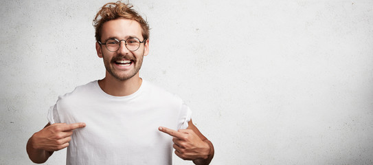 Horizontal shot of cheerful male with happy look points at white caual t shirt with copy space for your print or design. Bearded male nerd advertises new outfit, poses against blank white background
