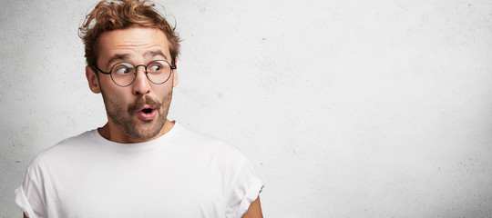 Horizontal shot of amazed bearded male has European appearance wears spectacles, looks in satisfaction aside, sees something wonderful and amazing, poses against white background with copy space Wall mural