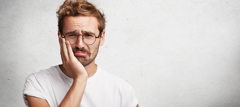 Discontent sorrorful male has terrible toothache, can`t stand pain, being upset, poses against white background with copy space for your advertising content. Upset unhappy man has some troubles