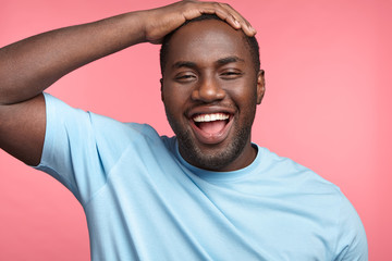 Joyful glad black cheerful black man being satisfied with results of work, closes eyes with happiness, keeps hand on head, isolated over pink background. African American male has good mood. Fotobehang