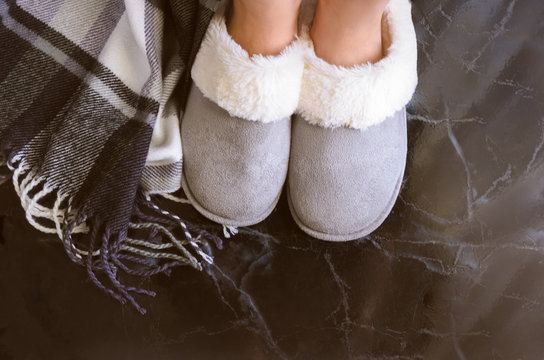 Female legs in cozy slippers on mramor  floor with cashmere blanket. Woman wearing  warm and comfortable slippers on the morning. Relax and stay at home concept. Copy space.