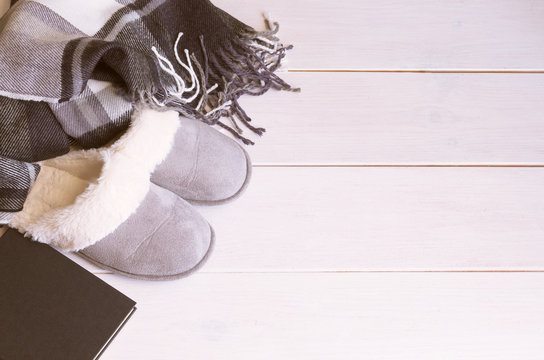 Woolen warm blanket, book and  cozy home slippers on wooden floor. Relax and stay at home concept. Copy space.
