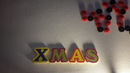 Colored letters spell out Xmas on white canvas with Christmas gifts