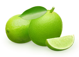 Lime fruit with green leaf next to lying and slice