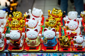 Chinese. Japanese souvenirs. Figurine white and golden cats brings good luck. Golden Maneki Neko cat or Welcome mascot
