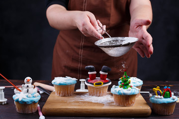 Holiday party treats making. Woman sprinkling sugar powder on decorated cupcakes. Festive food, cooking process, family culinary, Christmas and New Year celebration traditions concept