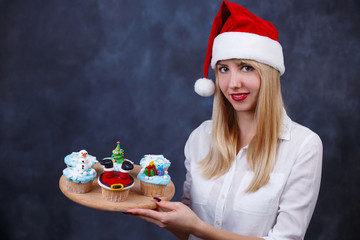 Young beautiful woman confectioner in Santa cap with decorated Christmas cupcakes set in hands on studio background, free space for text design. New Year, party, treats, sweets, celebration concept