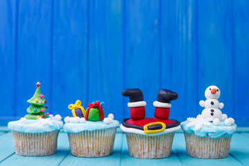 Delicious New Year or Christmas cupcakes set with bright decorations made of confectionery mastic. Festive sweets, homemade confectionery, holiday food, party treats, celebration concept