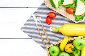 Healthy food for picnic. Sanwiches, fruits, vegetables, juice on tablecloth on white wooden background top view copyspace