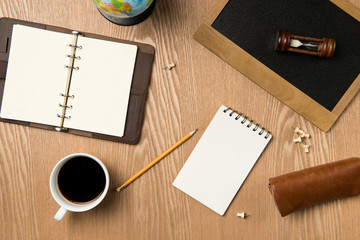 Business planning concept. Top view of hand writing on a blank notebook with hot coffee.