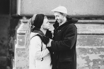 Couple has fun and laughs. kiss. Young hipster couple hugging each other in winter park. Winter love story, a beautiful stylish young couple. Winter fashion concept with boyfriend and girlfriend.