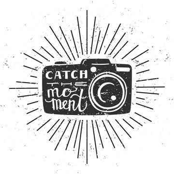 Catch the moment. Vector illustration with black silhouette of photo camera with hand written quote, scroll and sunburst on white background with grunge texture.