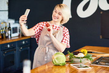 Attractive young woman with toothy smile wearing checked shirt and apron taking selfie on smartphone while holding fresh cherry tomatoes in hand, interior of modern kitchen on background