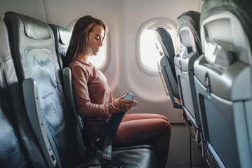 Girl is strapped on the plane near window