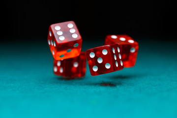 Photo of four playing red dices on green table