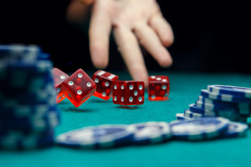 Image of man throwing dice on table with chips in casino