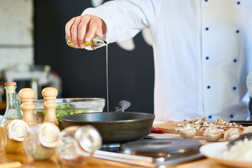 Close-up shot of unrecognizable chef wearing uniform pouring olive oil into frying pen while preparing mushrooms at modern restaurant kitchen